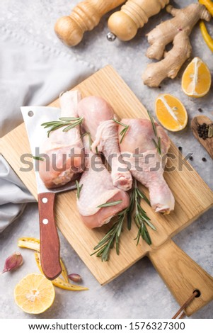 Raw organic uncooked chicken legs or drumsticks in pan with ingredients for cooking (pepper, lemon, rosemary, salt, garlic). Meat top view