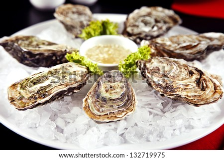 Raw oyster served with sauce on a plate with ice
