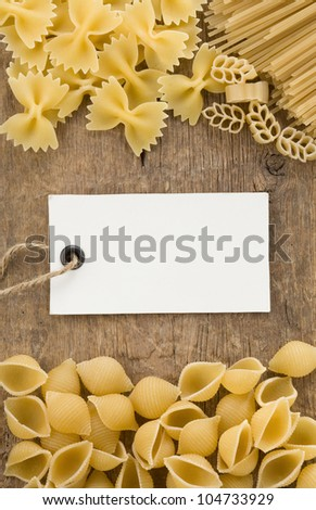raw pasta and price tag label on wooden background - stock photo