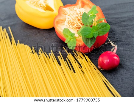 Raw pasta on the table with vegetables, papryka, radish and mint. Zdjęcia stock ©
