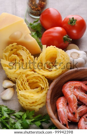 Raw pasta, shrimps, tomato, cheese and garlic. Ingridient for cooking pasta with shrimps and tomato