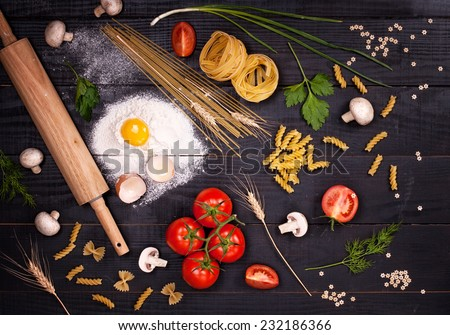 Raw pasta, tomatoes,mushrooms, flour and eggs on black wooden table background, top view