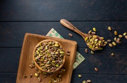 Raw peeled green pistachio nut in a wooden plate on a dark background. top view overhead view   copy space Close up view
