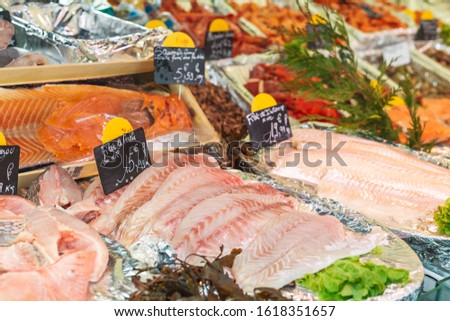 Raw perched fish fillet at the fish market with price tags. Large assortment of fresh chilled seafood, perched fish fillet, salmon. Keto food and healthy nutrition concept.