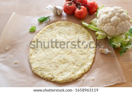 raw pizza base from shredded cauliflower on baking paper, healthy vegetable alternative for low carb and ketogenic diet, copy space, selected focus, narrow depth of field Foto stock ©