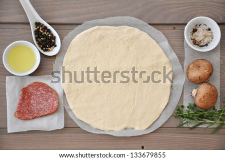 raw pizza ingredients - dough, cheese, mushrooms, salami and tomato