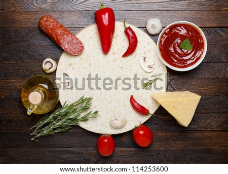 raw pizza ingredients - dough, sauce, cheese, mushrooms, salami and tomato