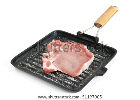 raw pork chop on a griddle with salt isolated on white background with clipping path