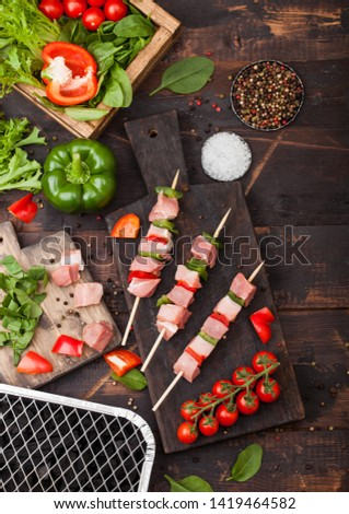 Raw pork kebab with paprika on chopping board with fresh vegetables and disposable charcoal grill on wooden background. Salt and pepper with lettuce and paprika pepper.
