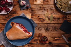 Raw pork knuckle on blue plate, seasonings, pepper set, bay, leaf, garlic, red onions on brown wooden table, top view. Cooking of meat dish, meal and flavourings, cuisine.