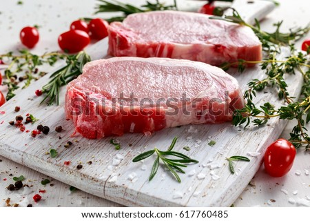 Raw Pork Loin chops on a cutting board with herbs, rosemary, thyme, chilli, salt, pepper on white cutting board.