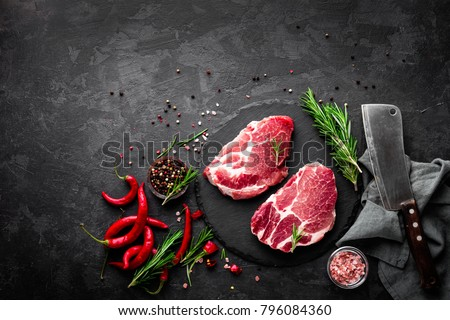 Raw pork meat. Fresh steaks on slate board on black background. Top view