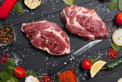 Raw pork meat on wooden cutting board at kitchen table for cooking pork steak roasted or grilled with ingredients herb and spices , Fresh pork