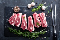 raw pork meat ribs with ingredients for cooking, dark background, top view