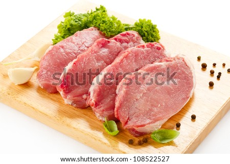 Raw pork on cutting board and vegetables