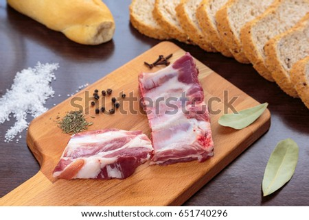 Raw pork ribs and spices over a cutting board, beside wholemeal bread slices  #651740296