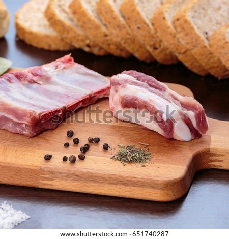 Raw pork ribs, black pepper and thyme over a wooden cutting board, in front of wholemeal bread slices #651740287