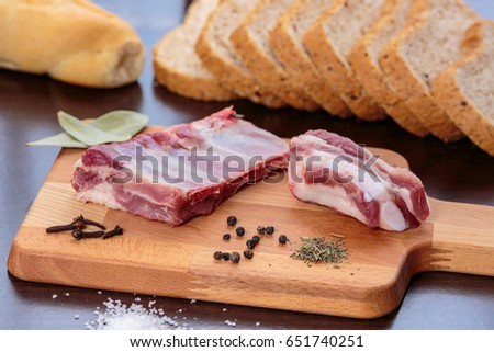Raw pork ribs, salt, cloves, bay leaves, black pepper and thyme over a wooden cutting board, in front of wholegrain bread #651740251