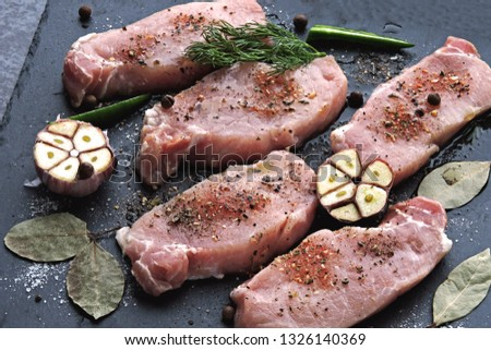 Raw pork steaks with garlic and spices on a stone board. The concept of cooking meat. Keto diet. Paleo diet. Pegan diet.