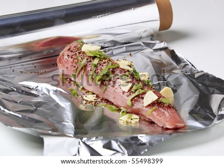 Raw pork tenderloin sprinkled with spices and garlic