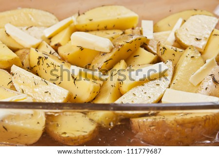 Raw potatoes in a glass tray marinated with olive oil, butter slices, thyme and salt, ready to be roasted