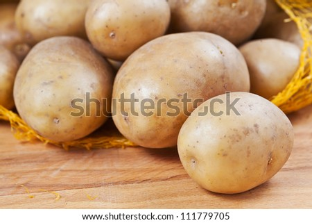 Raw potatoes in a yellow net sack