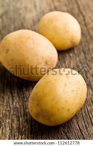 raw potatoes on old kitchen table