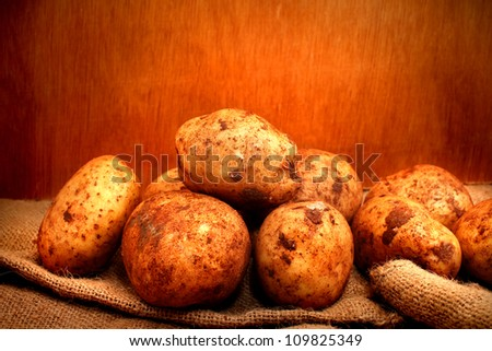 Raw Potatoes with soil on wooden box on gunny bag with wooden background