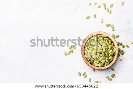Raw pumpkin seeds, food background, top view