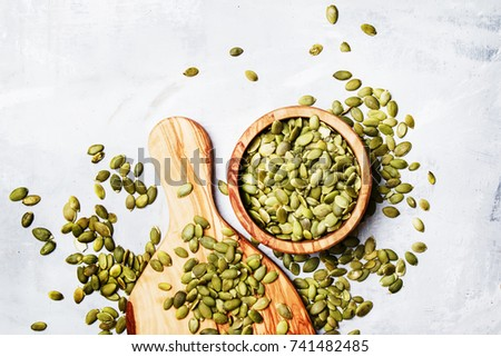 Raw pumpkin seeds, food background, top view #741482485