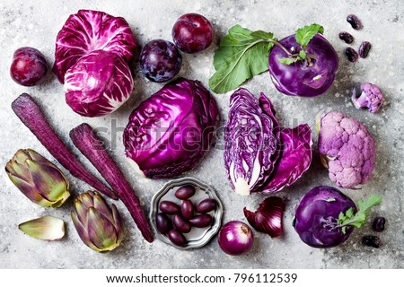 Raw purple vegetables over gray concrete background. Cabbage, radicchio salad, olives, kohlrabi, carrot, cauliflower, onions, artichoke, beans, potato, plums. Top view, flat lay.
