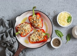 Raw quinoa stuffed sweet peppers in a cast iron skillet. Top view. Healthy, vegetarian food concept