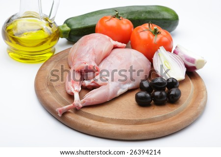 Raw rabbit legs with vegetables and olive oil on a wooden cutting board - stock photo