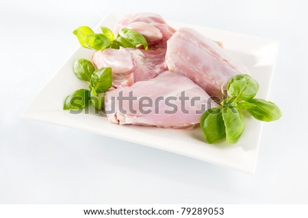 Raw rabbit meat on a plate. Arrangement with mint leaves.