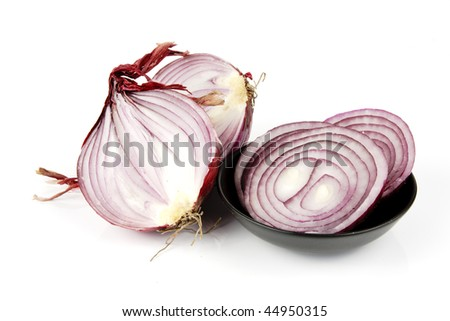 Raw red onion cut in half with slices in a small black dish on a reflective white background