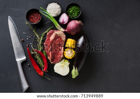 Raw rib eye steak with herbs and vegetables. Cooking ingredients for restaurant dish. Fresh meat, spices, eggplant, onion, chilli, corn on plate with knife on black background, copy space, top view