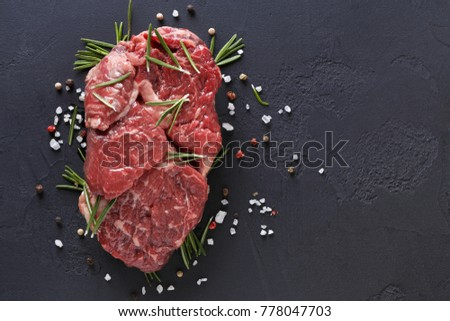 Raw rib eye steak with spices and vegetables. Ingredients for restaurant meal. Fresh meat, salt, rosemary, thyme, chilli, cherry tomatoes, garlic on black stone. Food background, copy space, top view #778047703