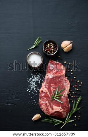 Raw ribeye beefsteak with seasonings, black wooden background, top view