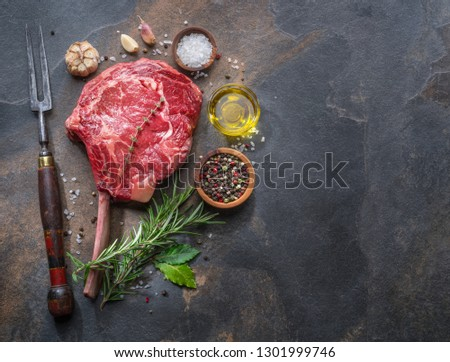 Raw  Ribeye steak or beef steak on the graphite cutting board  with herbs and spices. Top view.
