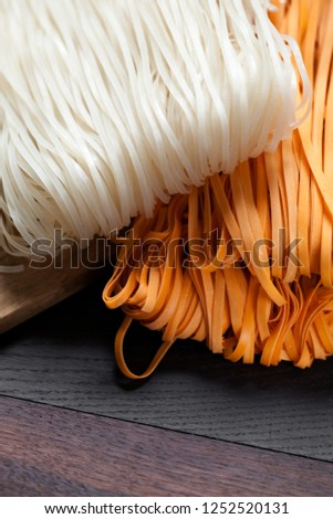 Raw rice flour noodles on wooden background , photographed overhead on dark wood with natural light (Selective Focus, Focus on the top of the noodles)