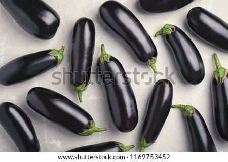 Raw ripe eggplants on light background, top view #1169753452