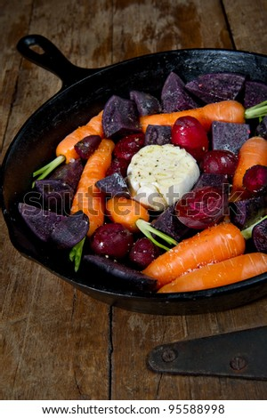 Raw root vegetables in a cast iron skillet ready for the oven and shot from above. Vegetables include carrots, red beets, garlic and purple potatoes.