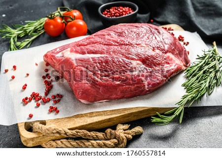 Raw Round beef cut on a cutting board. Black background. Top view Photo stock ©