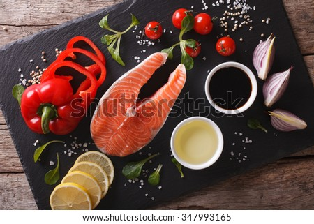 Raw salmon and ingredients on a slate board close-up on the table. Horizontal top view #347993165
