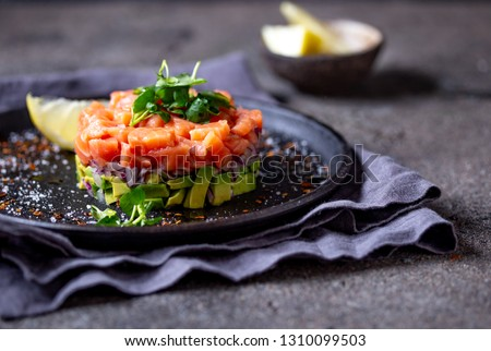 Raw salmon, avocado purple onion salad served in culinary ring on black plate. Black concrete background