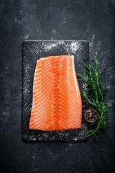 Raw salmon filet on dark slate background, wild atlantic fish