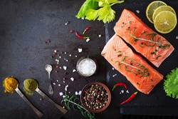 Raw salmon fillet and ingredients for cooking on a dark background in a rustic style. Top view