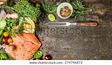 Raw salmon fillet with fresh seasoning, spices and fork on rustic wooden background, top view, banner for website with cooking concept