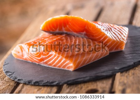 Raw Salmon fillets on slate and wooden board.