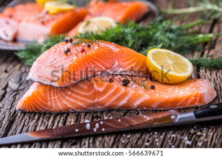 Raw salmon fillets pepper salt dill lemon and rosemary on wooden table.